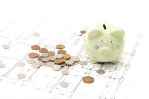 piggy bank over remodeling plans
