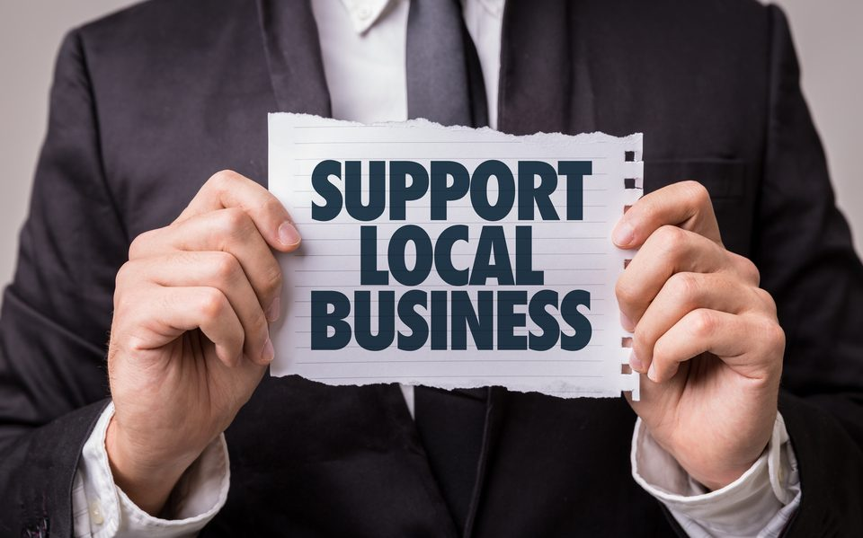 man holding a sheet of paper that says support local business
